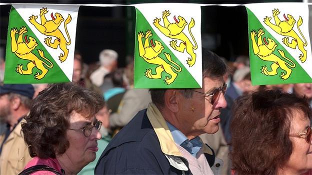 Männer und Frauen unter grün-gelb-weissen Kantonswappen.