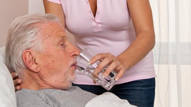 Alter Mann wird von Enkelin gepflegt.
