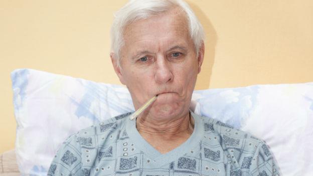 Älterer Mann im Bett mit Fiebermesser.