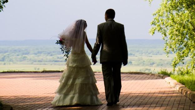 Ehepaar nach Hochzeit von hinten fotografiert.