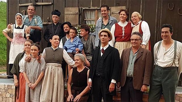 Eine Gruppe von Laiendarstellerinnen und -darstellern in historischen Kostümen.