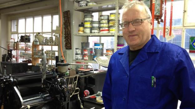 Mann im blauen Arbeitskittel steht in Werkstatt.