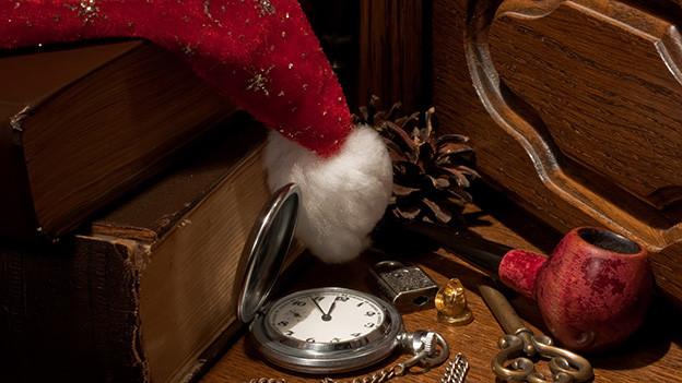 Stillleben mit Weihnachtsmann-Mütze, alter Uhr und Tabakpfeife.