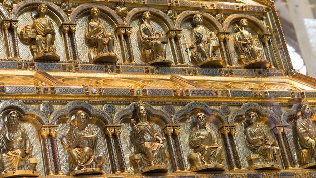 Ein Schrein aus Gold mit verschiedenen sitzenden Figuren.