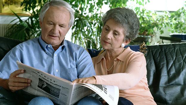 Ein älteres Ehepaar sitzt auf einem Sofa und studiert mit ernstem Blick die Zeitung.