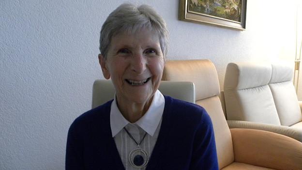 Die Seniorin mit kurzen grauen Haaren trägt eine dunkelblaue Strickjacke über einer weissen Bluse und sitzt in einem Wohnzimmer vor einem hellen Ledersessel.