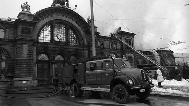 Schwarz-Weiss-Fotografie mit einem Löschfahrzeug, das vor einem Bahnhof steht.