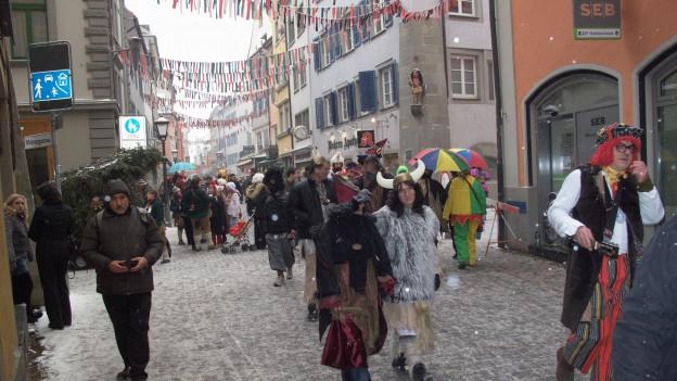 Maskierte Menschen schlendern durch die Altstadt.