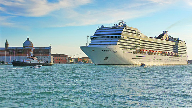 Ein grosses Kreuzfahrtschiff fährt in einen Hafen ein.