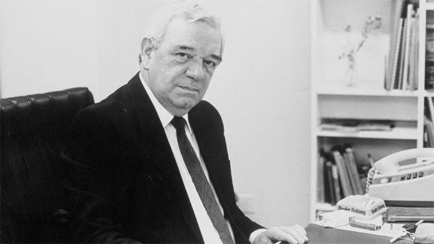 Schwarz-Weiss-Fotografie von einem Mann, der an einem Schreibtisch vor einem Stapel Papieren sitzt.