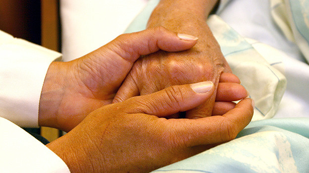 Zwei Paar übereinander liegende Hände.