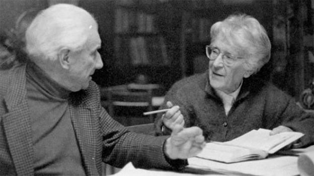 Ein älterer Mann und eine ältere Frau sitzen diskutierend an einem Tisch.
