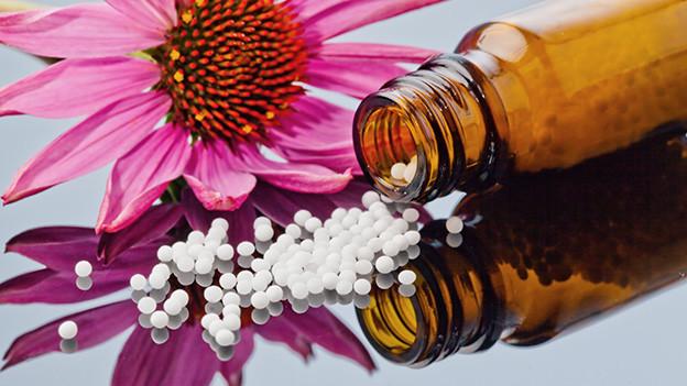 Vor einer rosa Anemone liegt ausgeschüttet aus einer kleinen braunen Flasche ein Haufen weisser Kügelchen.