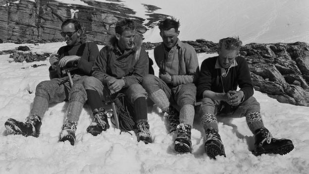 Schwarz-Weiss-Fotografie mit den vier Bergsteigern, die am Berg im Schnee sitzen.