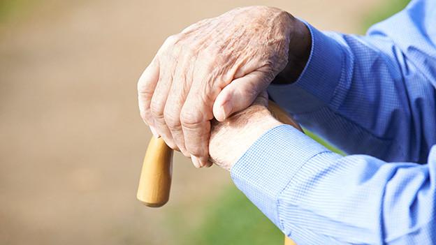 Auf einen Stock gestützte Hände eines alten Mannes.