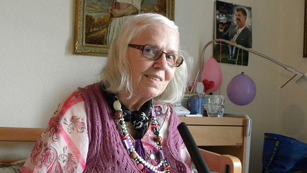 Die grauhaarige Rentnerin trägt eine Brille sowie Kleider in rosa Tönen und sitzt in ihrem Wohnzimmer.