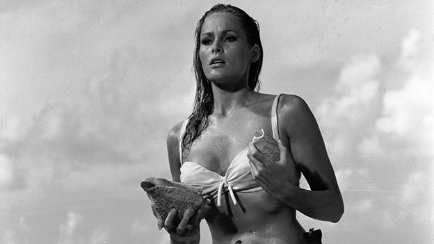 Schwarz-Weiss-Fotografie mit einer blondhaarigen Frau im Bikini, die am Strand steht und grosse Muscheln in den Händen hält.
