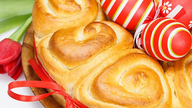 In der Mitte eines kranzförmigen Brotes liegen farbige Ostereier.
