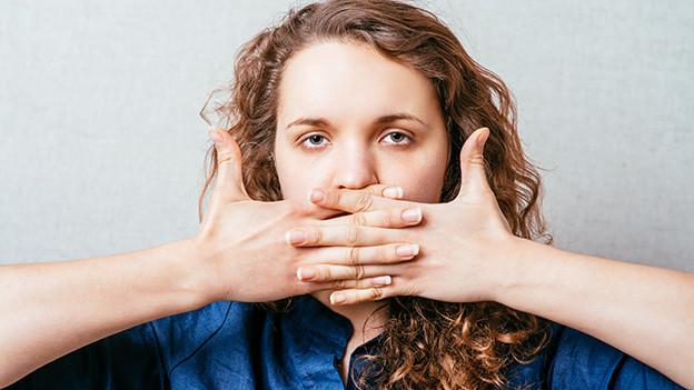 Eine junge Frau hält sich beide Hände vor den Mund.