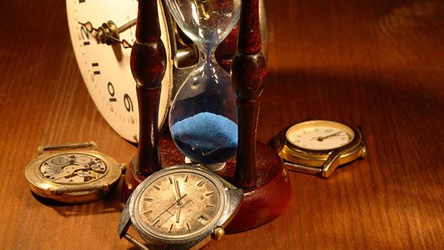Ein paar alte Uhren liegen auf einem Tisch, auf dem eine Sanduhr steht.
