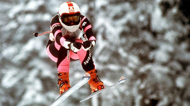 Skifahrerin im Rennanzug beim Sprung während einer Abfahrt.