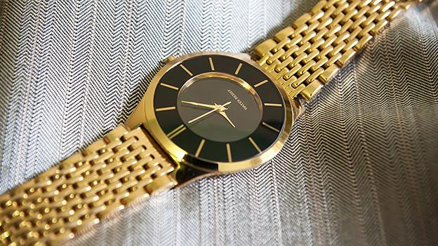 Eine goldene Uhr liegt auf edlem Stoff.