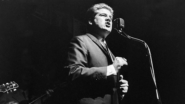 Schwarz-Weiss-Fotografie mit dem Sänger vor dem Mikrofon.