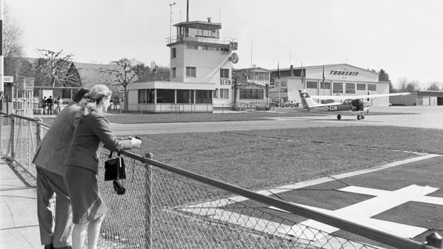Besucher stehen am Rand des Rollfelds des Flughafens Bern-Belpmoos (Aufnahme von 1972).