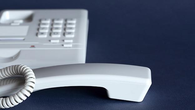 Der Hörer eines weissen Telefons liegt auf einem Tisch.