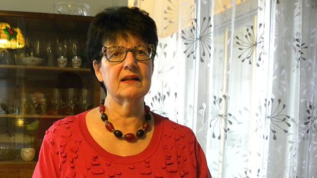 Die dunkelhaarige Frau trägt einen roten Pullover und sitzt in ihrem Wohnzimmer am Esstisch.