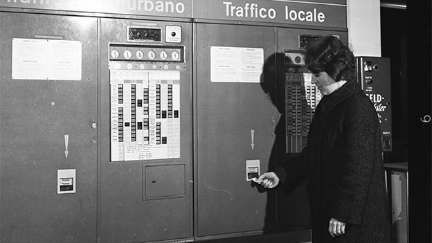 Historische Aufnahme mit einer Frau, die vor einem grossen Billettautomaten steht.