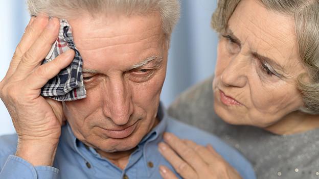 Ein älterer Mann fühlt sich krank und wird von seiner Frau getröstet.