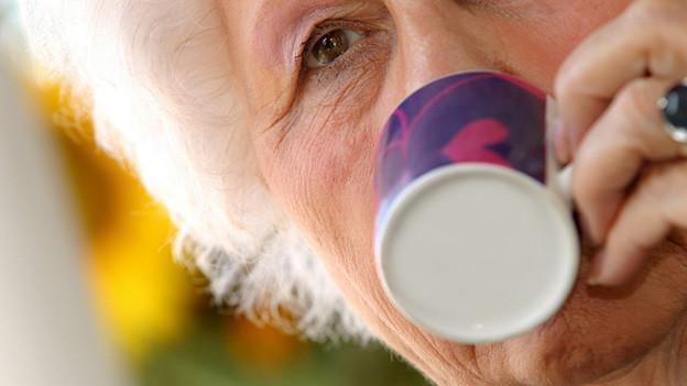 Grossaufnahme einer älteren Frau, die aus einer farbigen Tasse trinkt.