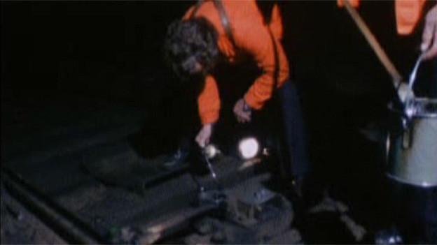 Ein Mann mit leuchtend oranger Jacke beugt sich zum Gleis hinunter.