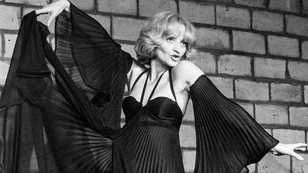Schwarz-Weiss-Fotografie mit der Schauspielerin im langen wallenden schwarzen Kleid.
