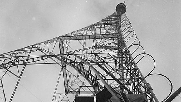 Schwarz-Weiss-Fotografie mit Blick von unten auf einen Stahlfachwerkturm.