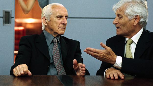 Zwei ältere Männer diskutieren miteinander.