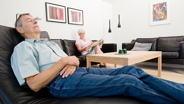 Ein Mann liegt in einem Lehnstuhl während eine Frau auf dem Sofa sitzend Zeitung liest.
