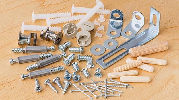 Schrauben, Dübel und Holzteile als Verbindungsstücke für Holzelemente.