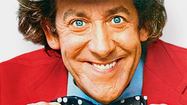Porträt eines lachenden Mannes mit grossen Augen.