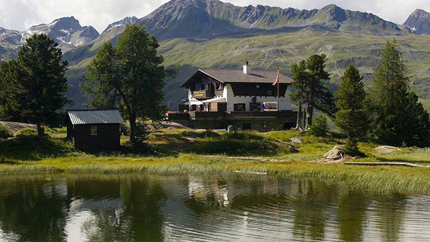 Ein Chalet am Ufer eines Bergsees.