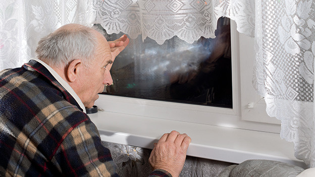 Ein alter Mann blickt neugierig aus dem Fenster hinaus in die dunkle Nacht.