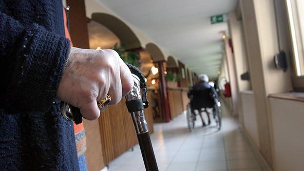 Hand einer alten Frau, die auf dem Flur eines Pflegeheims an einem Stock spazieren geht.
