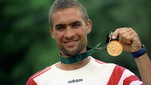 Der strahlende Olympiasieger Xeno Müller zeigt seine Goldmedaille.