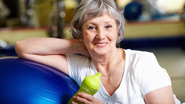 Eine ältere Frau sitzt mit einer Trinkflasche zufrieden vor einem Gymnastikball.