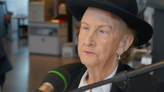 Eine ältere Frau mit schwarzem Hut.