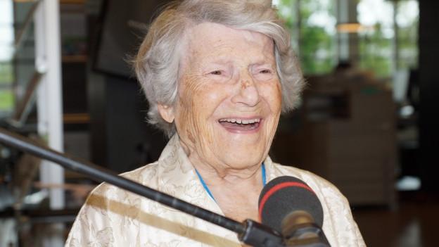 Simone Enderle beim Interview am runden Tisch von Mikrofon sitzend.