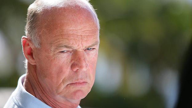 Ein älterer Mann mit einem griesgrämigen Gesicht.