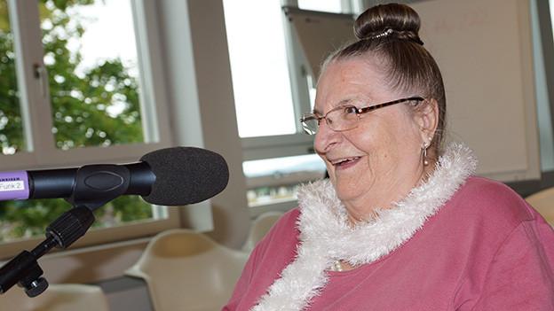 Eine fröhliche Seniorin sitzt lachend vor einem Mikrofon.