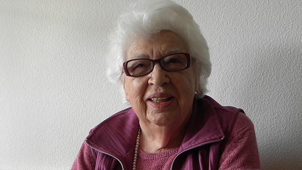 Die weisshaarige Seniorin trägt eine Brille und eine altrosa Jacke über einem altrosa Pullover.